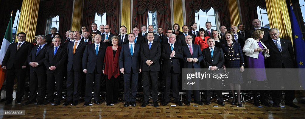 President of the European Commission Jose Manuel Barroso (C) is flanked by Irish Prime Minister Enda Kenny (CL) and Deputy Prime Minister Eamon Guilmore (CR) as he poses with members of the College of Commissioners and the Irish Government before a meeting at Dublin Castle in Dublin on January 10, 2013 as Ireland began its six-month presidency of the European Union. AFP PHOTO / ARTUR WIDAK