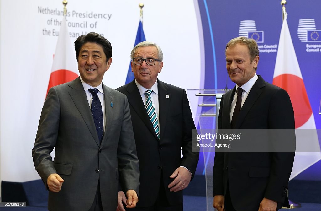 President of the European Council Donald Tusk (R) and President of the European Commission Jean-Claude Juncker (C) welcome Japanese Prime Minister Shinzo Abe prior to the EU - Japan leaders' meeting at the EU headquarters in Brussels on May 3, 2016.