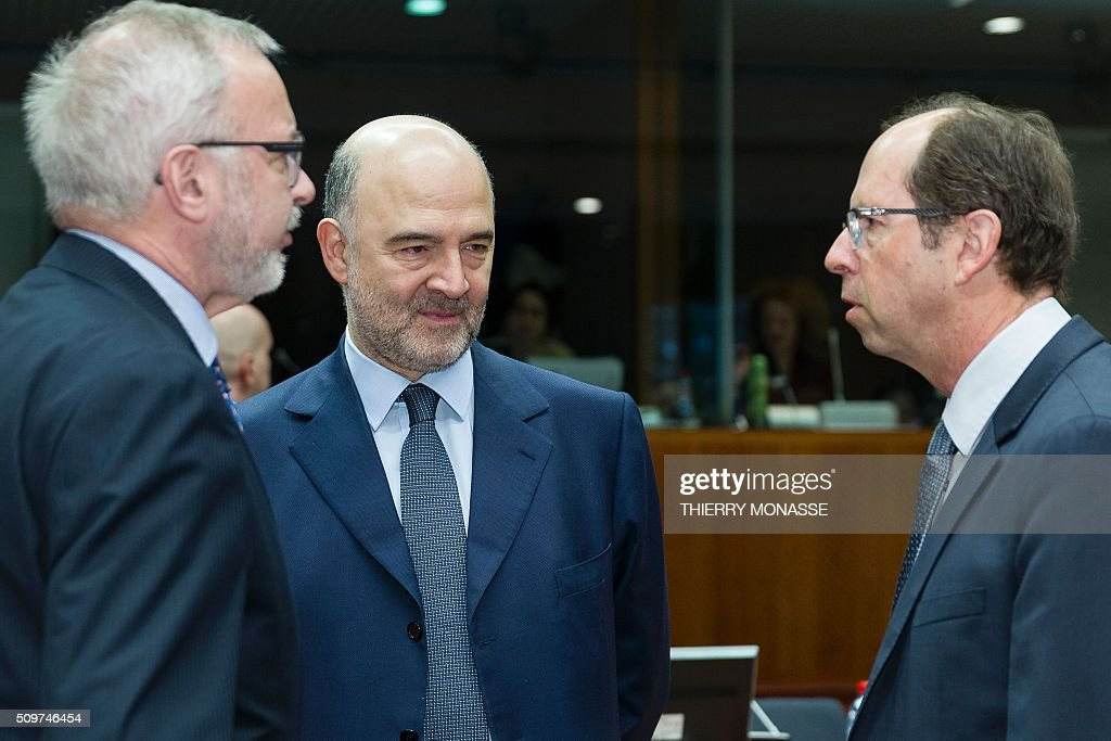 President of the European Investment Bank (EIB) Werner Hoyer (L) talks with European Commissioner for Economic and Financial Affairs, Taxation and Customs Pierre Moscovici (C) and Slovenia's Finance Minister Dusan Mramor prior to the start of the European Union Eco-Finance Council meeting at the EU Council building in Brussels on February 12, 2016. AFP PHOTO / THIERRY MONASSE / AFP / THIERRY MONASSE
