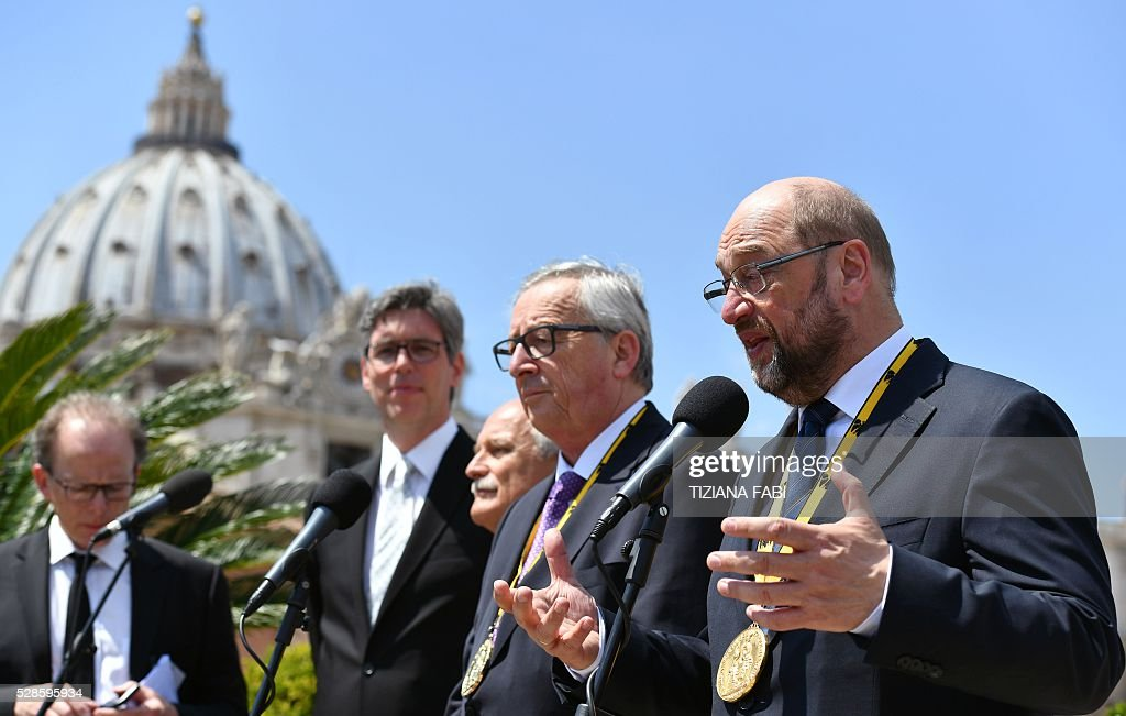 President of the European Parliament Martin Schulz (R), flanked by European Commission President Jean-Claude Juncker (2nd R), speaks during a press conference on May 6, 2016 in Rome, at the end of the award ceremony of the Charlemagne Prize. Pope Francis was presented with the EU's Charlemagne Prize for his contribution to European unification. European Commission President Jean-Claude Juncker and European Parliament President Martin Schulz explained the decision to give the award to such a regular and prominent critic of the EU in a column for France's Le Monde. / AFP / TIZIANA