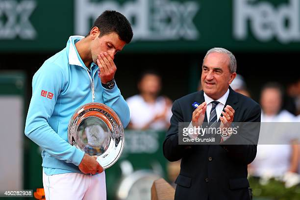 President of the FFT Jean Gachassin applauds Novak Djokovic of Serbia after his defeat in the men's singles final match against Rafael Nadal of Spain...