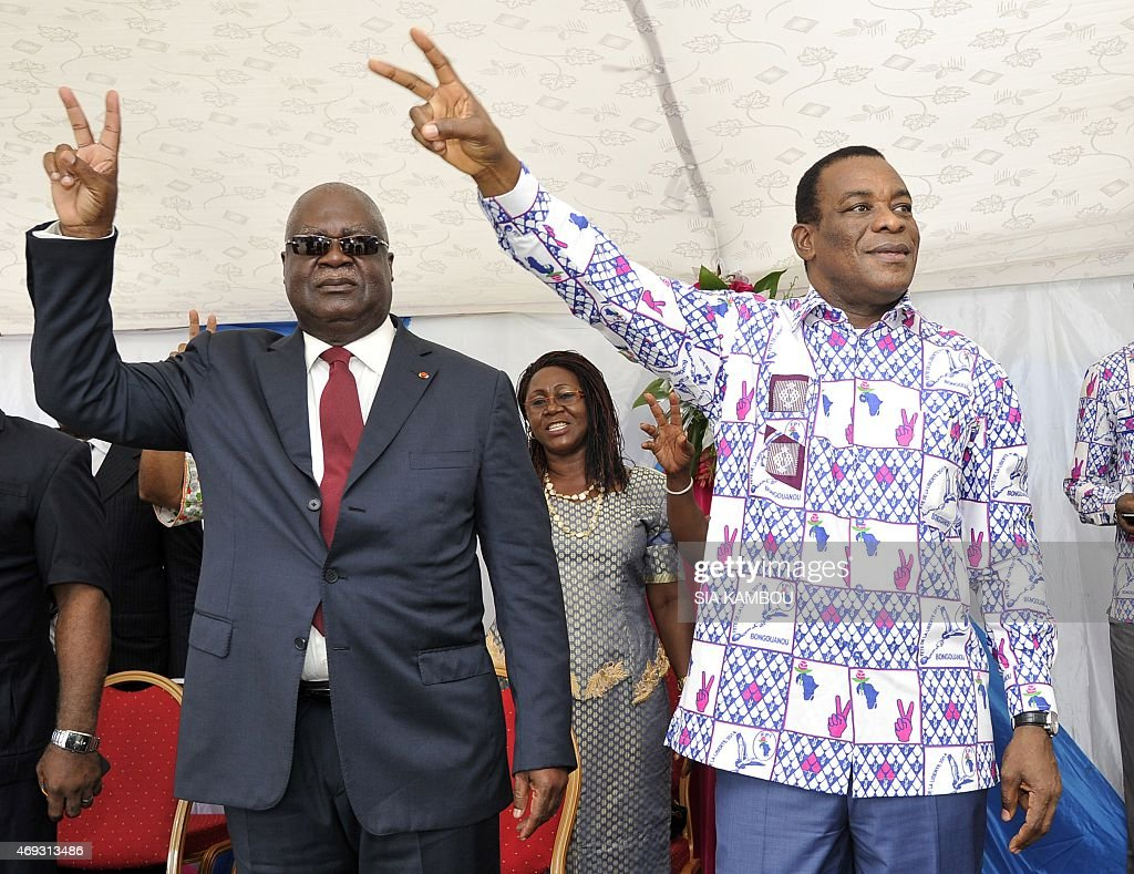 President of the FPI (Ivorian Popular Front) Pascal Affi N'guessan (R) and Vice-President of the FPI Marcel Gossio (L) gesture at the the party headquarter on April 11, 2015 in Abidjan to commemorate the anniversary of the arrest of Ivory Coast's former president and FPI member Laurent Gbagbo by the International Criminal Court of The Hague, on charges of crimes against humanity after post-election violence in 2011.