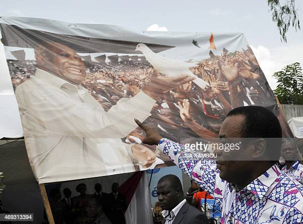 President of the FPI Pascal Affi N'guessan gestures in front of a banner picturing Ivory Coast's former president and FPI member Laurent Gbagbo at...