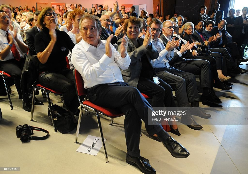 President of the French centrist party Modem François Bayrou (C) applauds during his party's meeting in Guidel, western France, on September 29, 2013. Bayrou said on September 29 that French President Francois Hollande hadn't achieved his 'promises' and praised German chancellor Angela Markel's 'courage'.