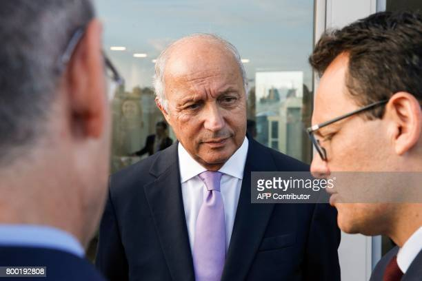 President of the French Constitutional council Laurent Fabius speaks with guest during a meeting with US actor and founder of the R20 climate action...