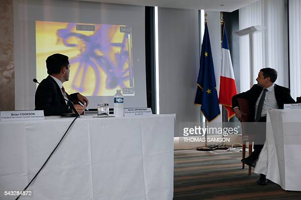 President of the French cycling federation David Lappartient and French Minister for Higher Education and Research Thierry Mandon look at a screen...