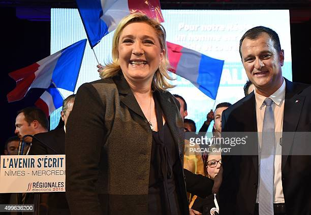 President of the French farright Front National party Marine Le Pen and her companion the party's vicepresident Louis Aliot react during a campaign...