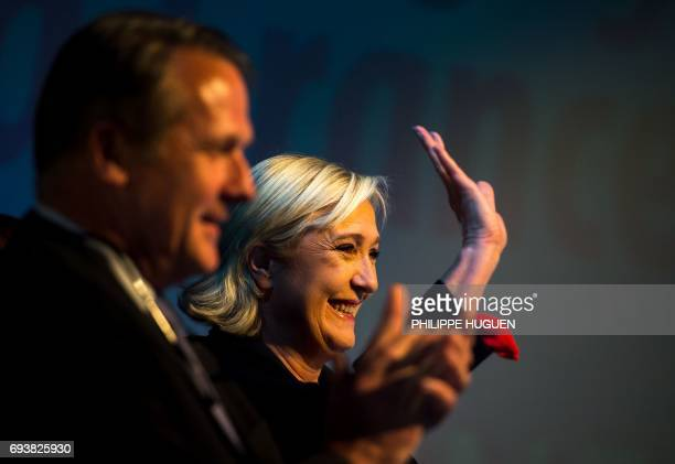 President of the French farright Front National party Marine Le Pen waves next to her brotherinlaw and advisor Philippe Olivier during a campaign...