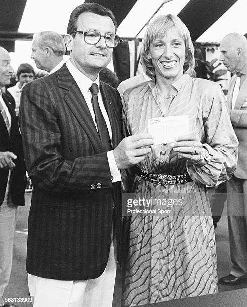 President of the French Tennis Federation Philippe Chatrier presents tennis player Martina Navratilova with a check for one million dollars after...
