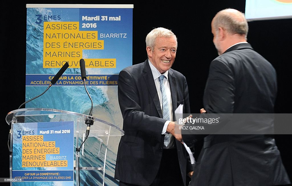 President of the French Union of Renewable Energy Jean-Louis Bal shakes hands with president of the French environment, energy and sustainable development implementation agency ADEME, Bruno Lechevin, during the third French National Conference of Renewable Marine Energy on May 30, 2016, in Biarritz, southwestern France. / AFP / IROZ