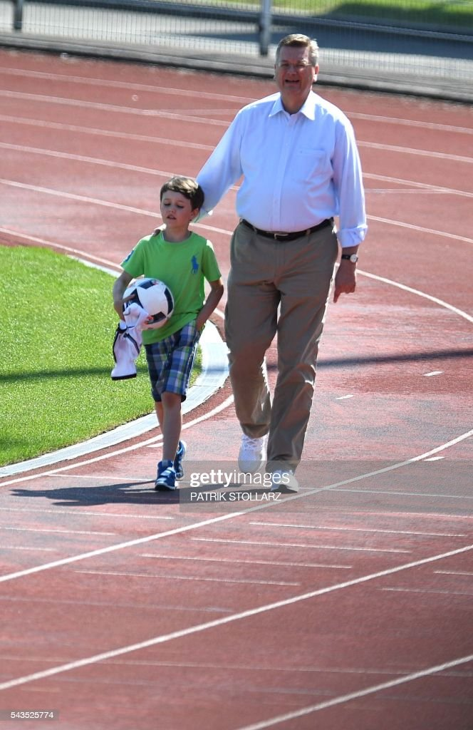 President of the German Football Federation Reinhard Grindel and his son Gustav arrive to attend a training session of the German team at the team's training grounds in Evian-les-Bains on June 29, 2016 during the Euro 2016 football tournament. / AFP / PATRIK
