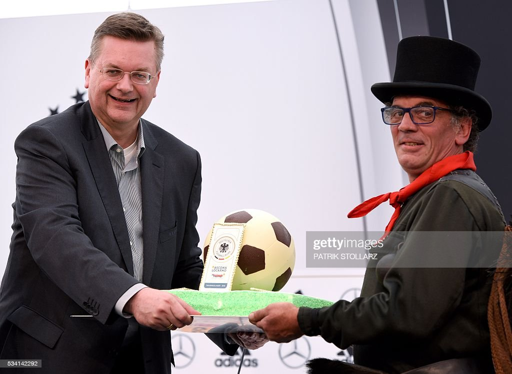 President of the German Football Federation Reinhard Grindel (L) receives a cake by a swiss chimney sweeper on the sideline of the team's preparation for the upcoming Euro 2016 European football championships, on May 25, 2016 in Ascona. STOLLARZ