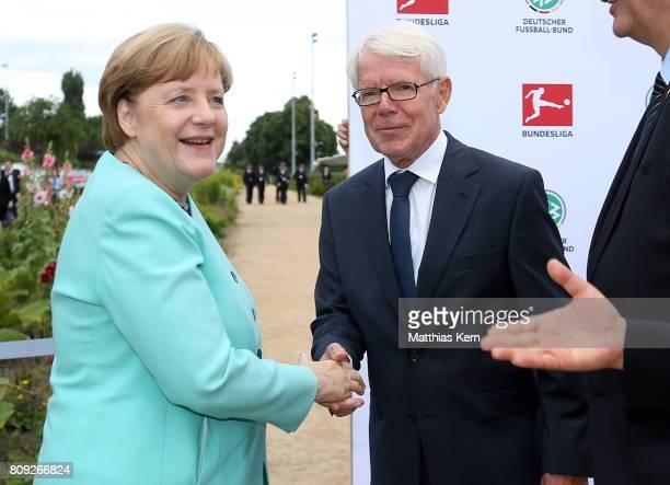 President of the German Football League Reinhard Rauball greets German Chancellor Angela Merkel during the Chinese German football summer camp at...