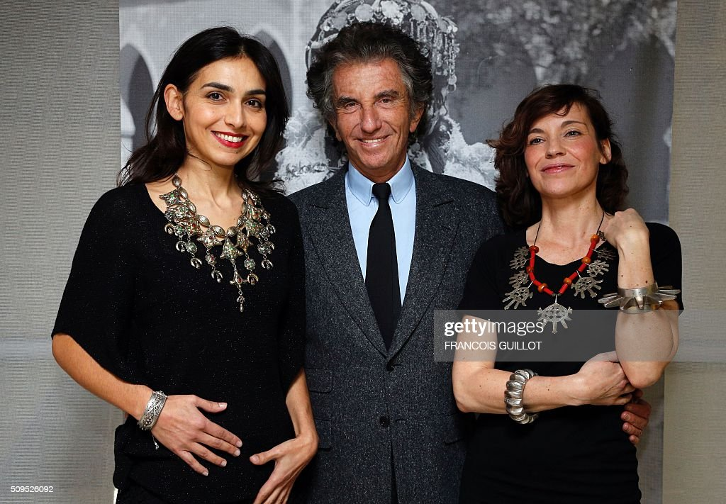 President of the Institut du Monde Arabe (Arab World Institute) Jack Lang (C), poses with pianist Charlotte Reinhardt (L) and French actress Elodie Mennegand both wearing jewelry from the exhibition 'Tresors a porter' during its opening at the Institut du Monde Arabe in Paris on February 11, 2016. / AFP / FRANCOIS GUILLOT