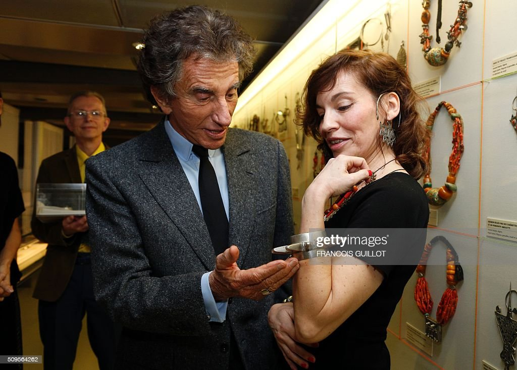 President of the Institut du Monde Arabe (Arab World Institute) Jack Lang (L) shows jewelry from the exhibition 'Tresors a porter' (jelwery to wear) wearing by French actress Elodie Mennegand at the Institut du Monde Arabe in Paris on February 11, 2016. / AFP / FRANCOIS GUILLOT