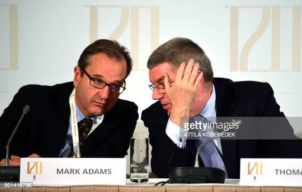 President of the International Olympic Committee Germany's Thomas Bach and IOC spokesman Mark Adams chat during a press conference in Budapest on...