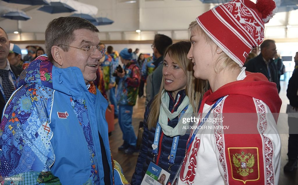 President of the International Olympic Committee (IOC) Thomas Bach (L) meets with ice hockey player Iya Gavrilova (R) and US skater Anna Ringsred during a visit at the Olympic Village on February 4, 2014 in Sochi before the start of the 2014 Sochi Winter Olympic Games.