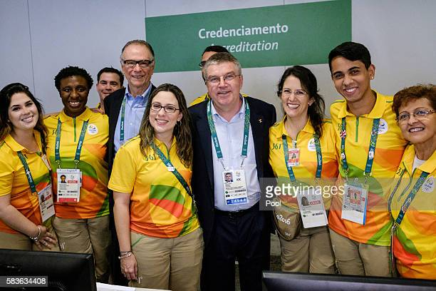 President of the International Olympic Committee Thomas Bach poses with volunteers after receiving his credential card on his arrival for Rio 2016...