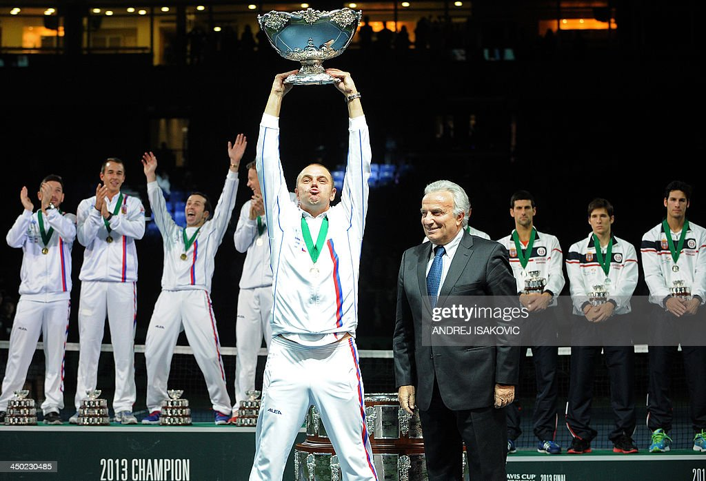 President of the International Tennis Federation Francesco Ricci Bitti (R) hands over the Davis Cup trophy to Czech Republic's team captain Vladimir Safarik (C) after Czech team won the Davis Cup tennis match finals against Serbia at the Kombank Arena in Belgrade on November 17, 2013. The Czech Republic defended the Davis Cup title after Radek Stepanek beat Serbian youngster Dusan Lajovic in the decisive fifth final rubber in straight sets on November 17, 2013.