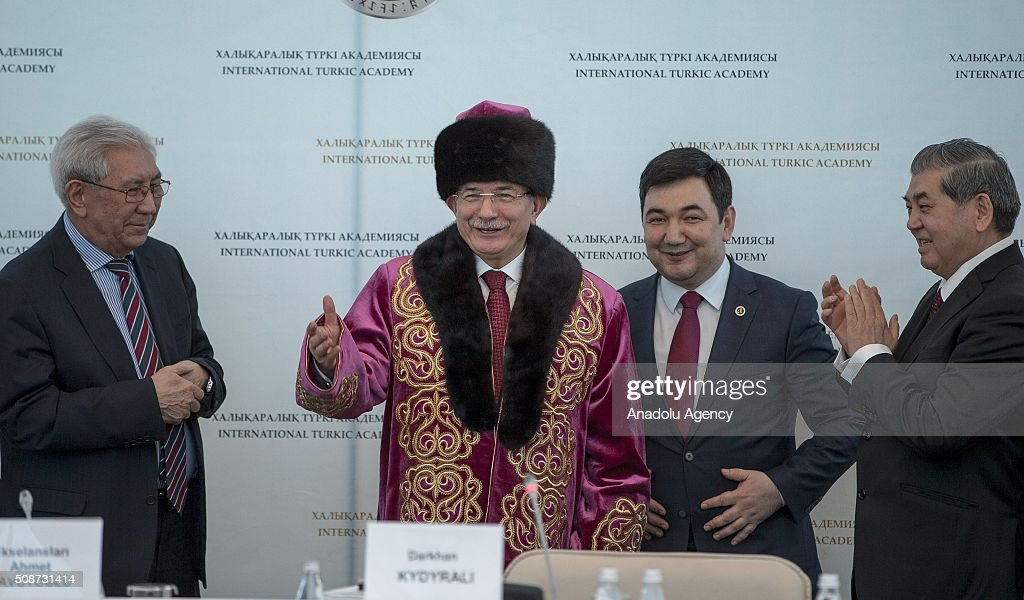 President of the International Turkish Academy Darkhan Kydyrali (R-2) give traditional clothes as a gift to Prime Minister of Turkey Ahmet Davutoglu (L-2) during the conference organized by Turkish academy at Peace and Reconciliation Palace in Astana, Kazakhstan on February 6, 2016.