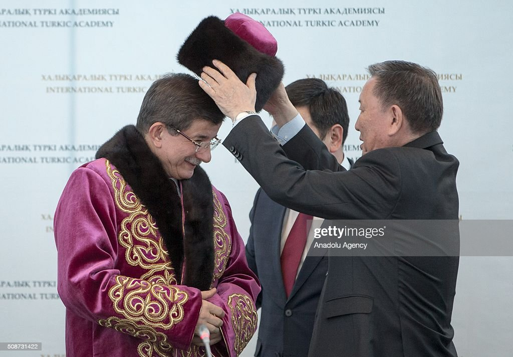 President of the International Turkish Academy Darkhan Kydyrali (R) give traditional clothes as a gift to Prime Minister of Turkey Ahmet Davutoglu (L) during the conference organized by Turkish academy at Peace and Reconciliation Palace in Astana, Kazakhstan on February 6, 2016.