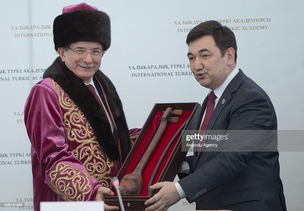 President of the International Turkish Academy Darkhan Kydyrali (R) gives a tratidional music instrument 'lute' as a gift to Prime Minister of Turkey Ahmet Davutoglu (L) during the conference organized by Turkish academy at Peace and Reconciliation Palace in Astana, Kazakhstan on February 6, 2016.