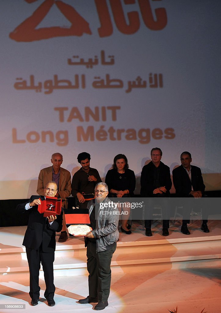 President of the Jury Mohamed Mediouni (L) presents Moroccan director Fawzi Ben Said (R) with the Silver Tanit award for his film ' Mort à vendre' (Death for Sale) during the closing ceremony of the 28th edition of the Cinematographic Days of Carthage (JCC) film festival on November 24, 2012, in Tunis.
