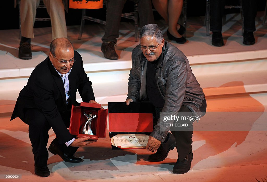 President of the Jury Mohamed Mediouni (L) presents Moroccan director Fawzi Ben Said (R) with the Silver Tanit award for his film ' Mort à vendre' (Death for Sale) during the closing ceremony of the 28th edition of the Cinematographic Days of Carthage (JCC) film festival on November 24, 2012, in Tunis. AFP PHOTO / FETHI BELAID