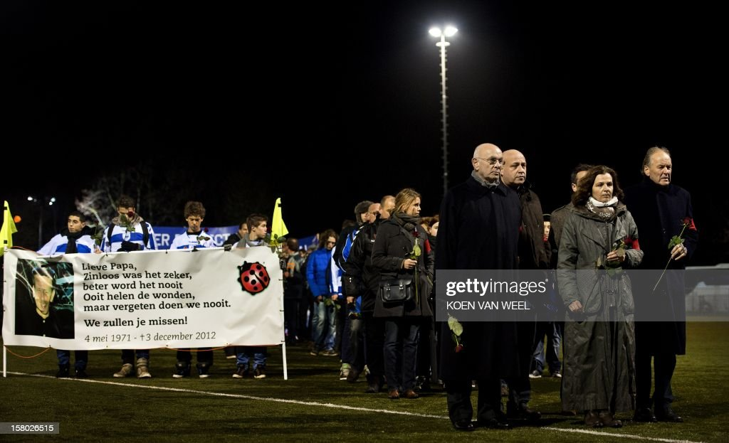 President of the KNVB Netherland's Michael van Praag (4R), and Minister of sports Edith Schippers (2R) lay flowers at the memorial site for the late linesman Richard Nieuwenhuizen at the SC Buitenboys clubhouse in Almere, on December 9, 2012. Nieuwenhuizen collapsed and fell into a coma after he was attacked by three teenagers at the end of a junior club football match on December 2, 2012. People gathered this afternoon for a silent march in memory of Nieuwenhuizen. AFP PHOTO / ANP / KOEN VAN WEEL netherlands out