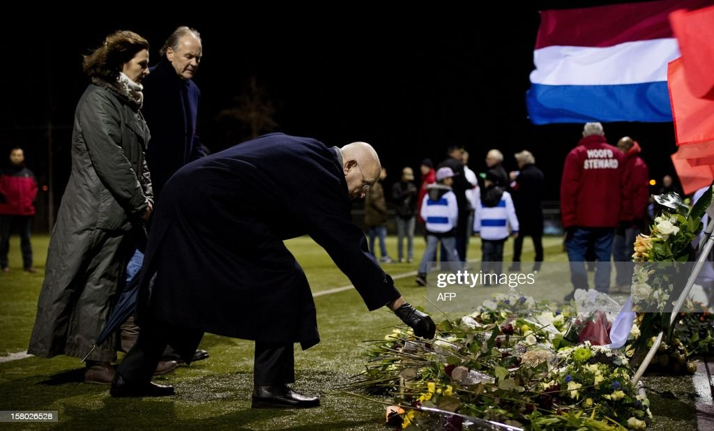 President of the KNVB Netherland's Michael van Praag (R), and Minister of sports Edith Schippers (2L) lay flowers at the memorial site for the late linesman Richard Nieuwenhuizen at the SC Buitenboys clubhouse in Almere, on December 9, 2012. Nieuwenhuizen collapsed and fell into a coma after he was attacked by three teenagers at the end of a junior club football match on December 2, 2012. People gathered this afternoon for a silent march in memory of Nieuwenhuizen. AFP PHOTO / ANP / KOEN VAN WEEL netherlands out