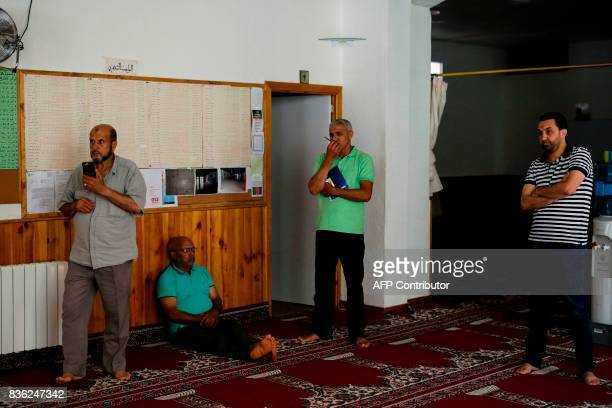 President of the muslim community of Ripoll Annour Ali Yassine waits next to other men before talking to the press at the mosque of Ripoll on August...