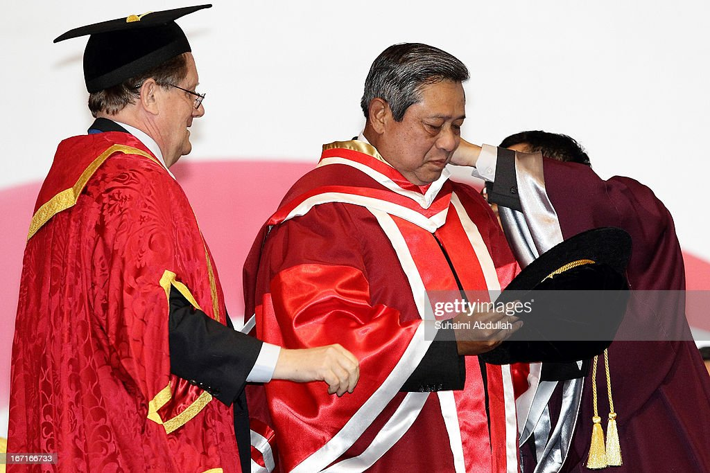 President of the Nanyang Technological University, Bertil Andersson (L) puts on the academic hood on the President of the Republic of Indonesia, Dr <a gi-track='captionPersonalityLinkClicked' href=/galleries/search?phrase=Susilo+Bambang+Yudhoyono&family=editorial&specificpeople=206513 ng-click='$event.stopPropagation()'>Susilo Bambang Yudhoyono</a> (C) during the honorary doctorate conferment ceremony on April 22, 2013 in Singapore. It is reported that President <a gi-track='captionPersonalityLinkClicked' href=/galleries/search?phrase=Susilo+Bambang+Yudhoyono&family=editorial&specificpeople=206513 ng-click='$event.stopPropagation()'>Susilo Bambang Yudhoyono</a> will hold a Leaders' Retreat with Singapore Prime Minister Lee Hsien Loong as part of the visit.