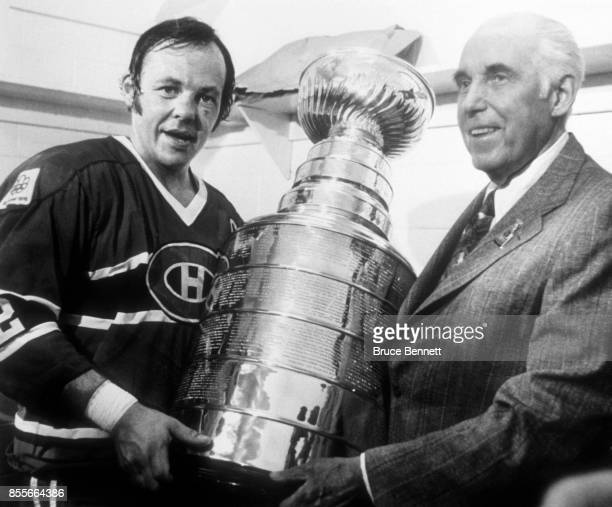 President of the National Hockey League Clarence Campbell presents Yvan Cournoyer of the Montreal Canadiens the Stanley Cup Trophy after Game 4 of...