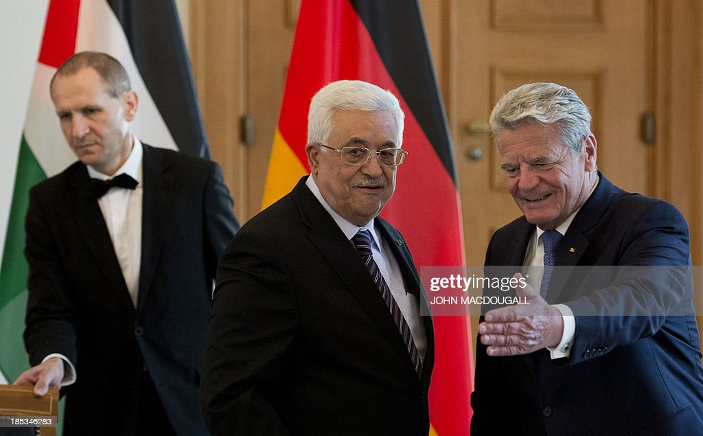 President of the Palestinian National Authority Mahmoud Abbas (C) is shown the way by German President Joachim Gauck (R) prior to talks at the presidential palace in Berlin October 19, 2013.