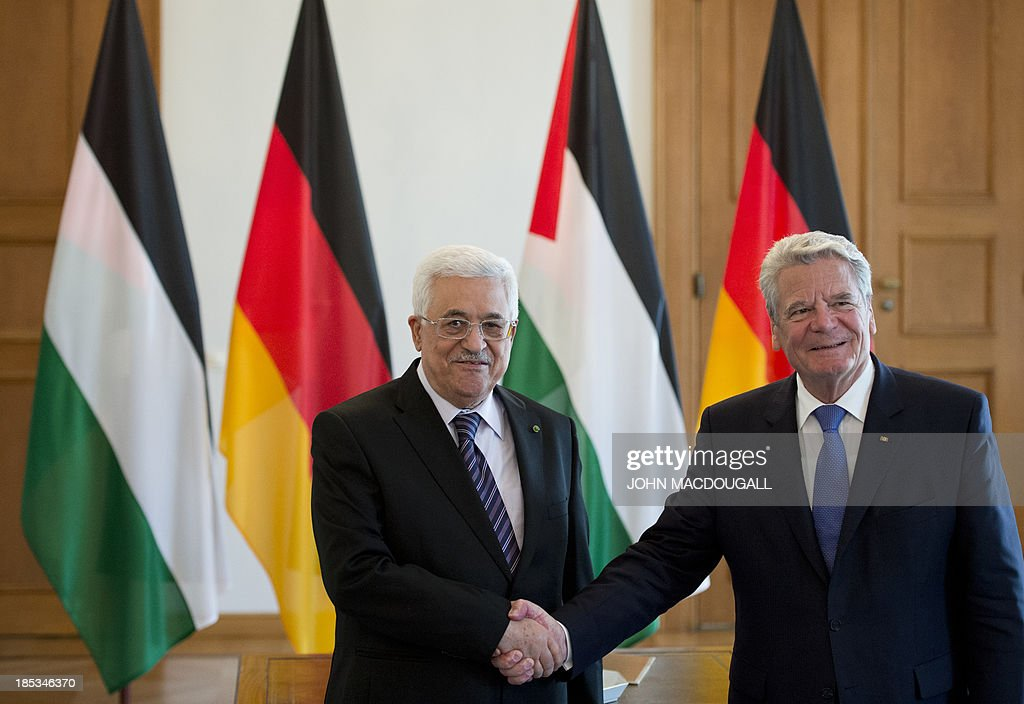 President of the Palestinian National Authority Mahmoud Abbas (L) shakes hands with German President Joachim Gauck prior to talks at the presidential palace in Berlin October 19, 2013. AFP PHOTO / JOHN MACDOUGALL