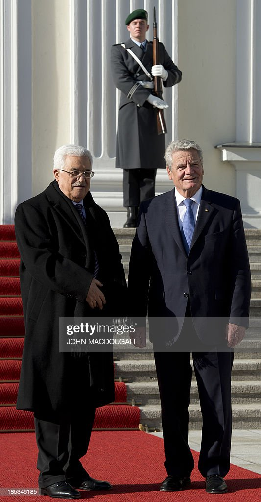 President of the Palestinian National Authority Mahmud Abbas (L) is greeted by German President Joachim Gauck prior to talks at the presidential palace in Berlin October 19, 2013. AFP PHOTO / JOHN MACDOUGALL