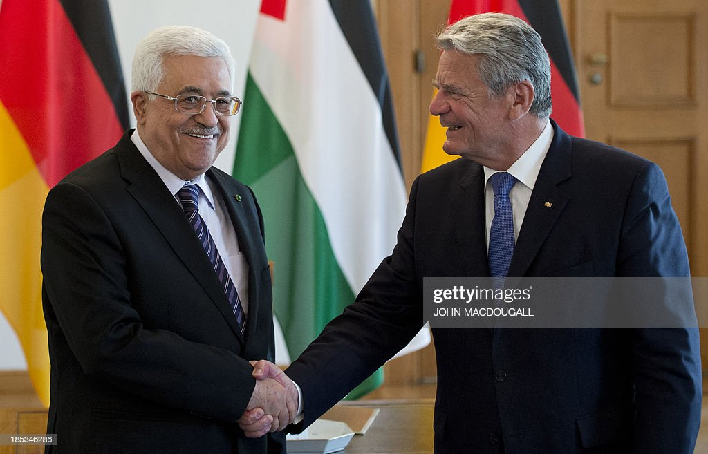 President of the Palestinian National Authority Mahmud Abbas (L) shakes hands with German President Joachim Gauck prior to talks at the presidential palace in Berlin October 19, 2013. AFP PHOTO / JOHN MACDOUGALL