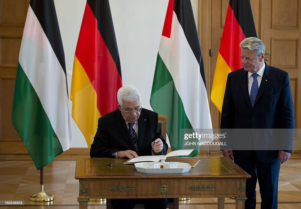 President of the Palestinian National Authority Mahmud Abbas (L) signs the official guest book as German President Joachim Gauck looks on prior to talks at the presidential palace in Berlin October 19, 2013.