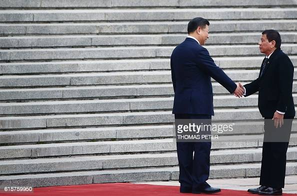President of the Philippines Rodrigo Duterte and Chinese President Xi Jinping shake hands as they attend a welcoming ceremony at the Great Hall of...