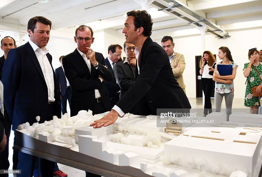 President of the Provence Alpes Cote d'Azur (PACA) region Christian Estrosi (L) listens to La friche belle de mai cultural site's director Alain Arnaudet showing a scale model on June 30, 2016 in Marseille, southern France. / AFP / ANNE