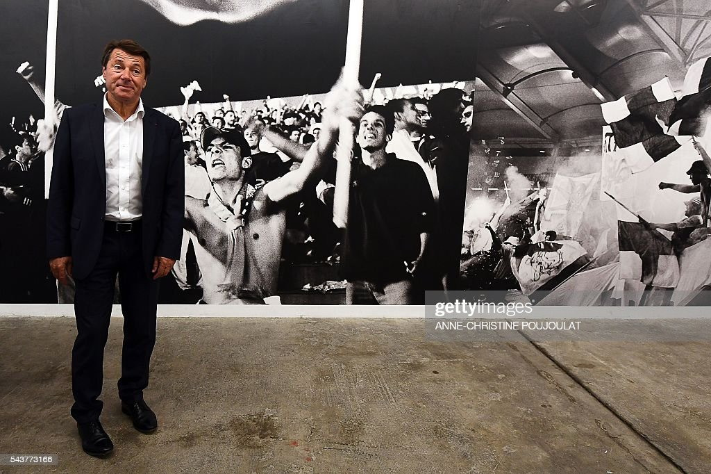President of the Provence Alpes Cote d'Azur (PACA) region Christian Estrosi poses in front of a picture as he visits a photo exhibition on the Olympique de Marseille (OM) football club supporters in La friche belle de mai cultural site on June 30, 2016 in Marseille, southern France. / AFP / ANNE