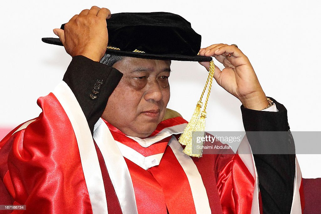 President of the Republic of Indonesia, Dr <a gi-track='captionPersonalityLinkClicked' href=/galleries/search?phrase=Susilo+Bambang+Yudhoyono&family=editorial&specificpeople=206513 ng-click='$event.stopPropagation()'>Susilo Bambang Yudhoyono</a> adjusts his doctoral hat during the honorary doctorate conferment ceremony on April 22, 2013 in Singapore. It is reported that President <a gi-track='captionPersonalityLinkClicked' href=/galleries/search?phrase=Susilo+Bambang+Yudhoyono&family=editorial&specificpeople=206513 ng-click='$event.stopPropagation()'>Susilo Bambang Yudhoyono</a> will hold a Leaders' Retreat with Singapore Prime Minister Lee Hsien Loong as part of the visit.