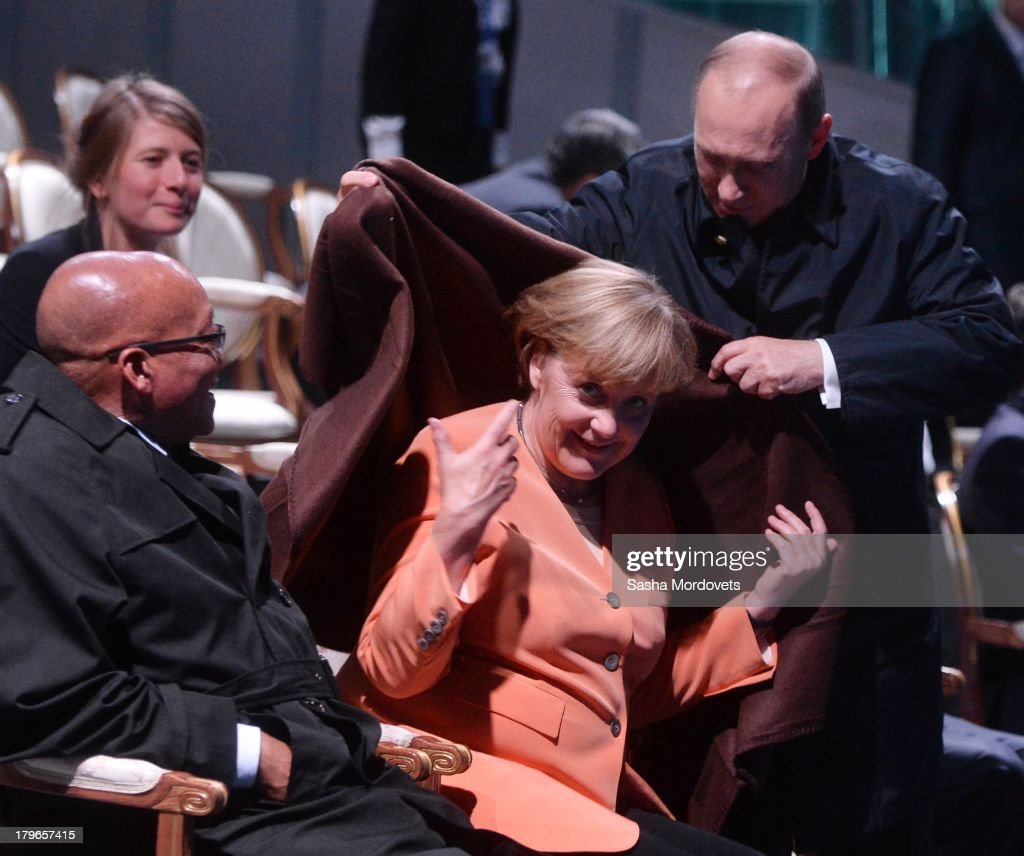President of the Russian Federation Vladimir Putin, helps Chancellor of Germany <a gi-track='captionPersonalityLinkClicked' href=/galleries/search?phrase=Angela+Merkel&family=editorial&specificpeople=202161 ng-click='$event.stopPropagation()'>Angela Merkel</a> with a coat as President of South Africa <a gi-track='captionPersonalityLinkClicked' href=/galleries/search?phrase=Jacob+Zuma&family=editorial&specificpeople=564982 ng-click='$event.stopPropagation()'>Jacob Zuma</a> looks on at the musical fountain show during the G20 summit on September 5, 2013 in St. Petersburg, Russia. The G20 summit is expected to be dominated by the issue of military action in Syria while issues surrounding the global economy, including tax avoidance by multinationals, will also be discussed during the two-day summit.