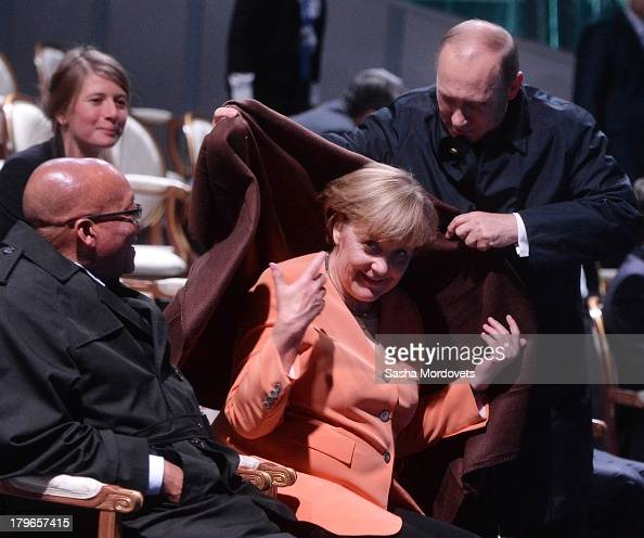 President of the Russian Federation Vladimir Putin helps Chancellor of Germany Angela Merkel with a coat as President of South Africa Jacob Zuma...
