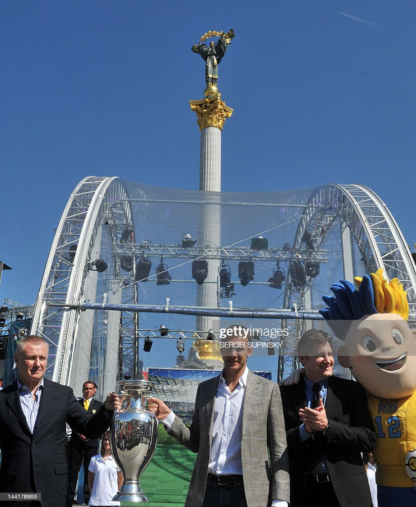 President of the Ukrainian Football Federation Grygoriy Surkis (L) and the National football team captain Andriy Shevchenko (C) hold an EURO 2012 tournament cup as former football player and UEFA ambassador Davor Suker (R) attends the Cup presentation on Independence square in Kiev on May 11, 2012 Along with tournament co-hosts Poland and Ukraine, European football's governing body UEFA has organised a five-week trophy tour in cities across the two countries.