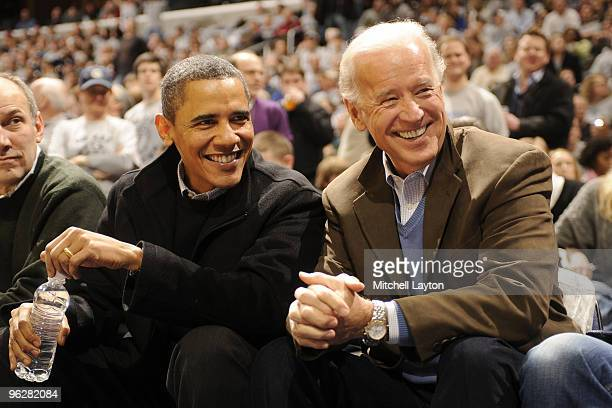 President of the United States Barack Obama and Vice President Joe Biden talk during a college basketball game between Georgetown Hoyas and the Duke...