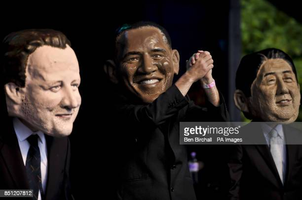 President of the United States Barack Obama raises his hands aloft as he and fellow G8 politicians are impersonated with large heads as they arrive...