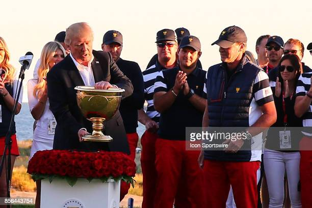President of the United States Donald Trump gives the Presidents Cup Trophy to Team USA Captain Steve Stricker after the Presidents Cup on October 1...
