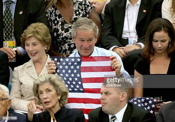 President of the United States George W Bush holds up the American flag while attending the swimming finals at the National Aquatics Center during...