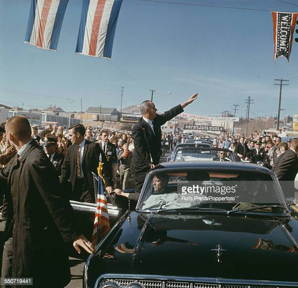 President of the United States Lyndon B Johnson pictured standing on the rear door of a Lincoln Continental limousine waving to supporters and crowds...